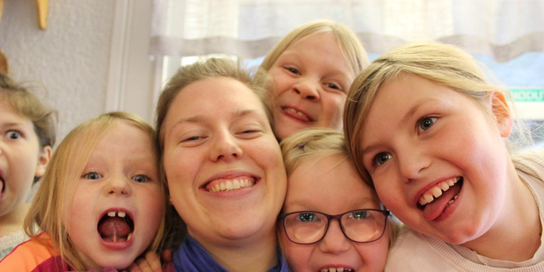 Bilde: Flere barn smiler og gjør grimaser, sammen med lederen sin. Bildet er en selfie.