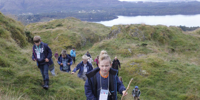 Bilde: Barn ute å går i naturen, med pilegrimsstav i hånda.
